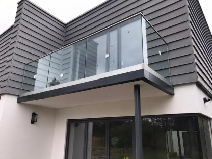 Frameless glass balustrade with stainless steel slotted channel tube top rail